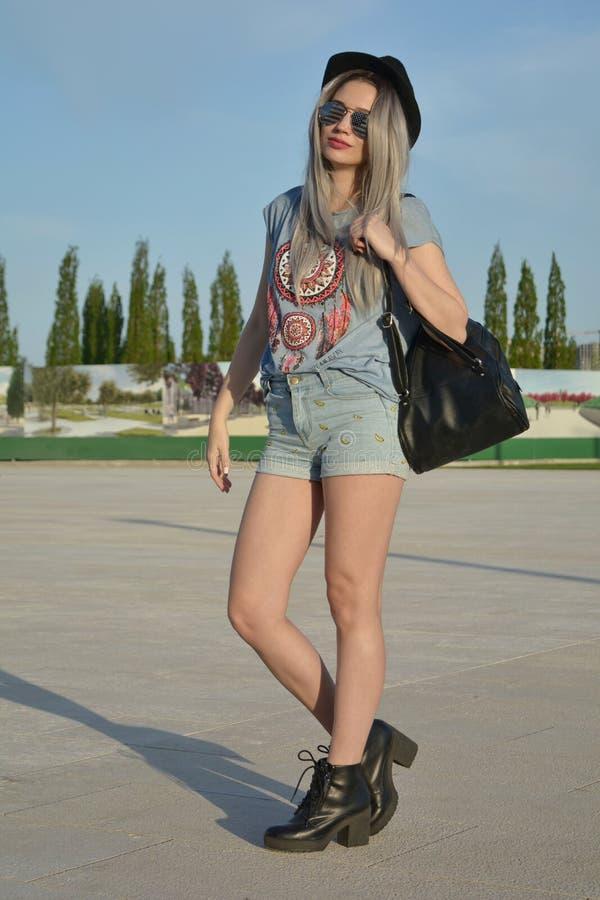 Mujer joven atractiva elegante que presenta en la calle que lleva pantalones cortos cortos y un sombrero negro imagenes de archivo