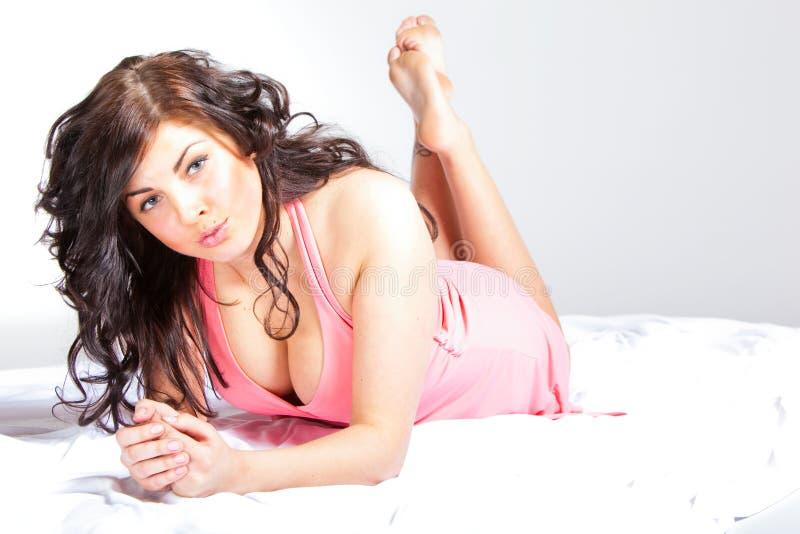 Mujer joven atractiva en alineada rosada foto de archivo