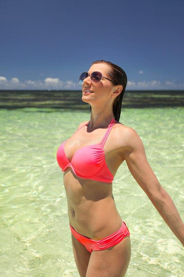 Mujer joven atractiva en biking rosado y gafas de sol fotografía de archivo