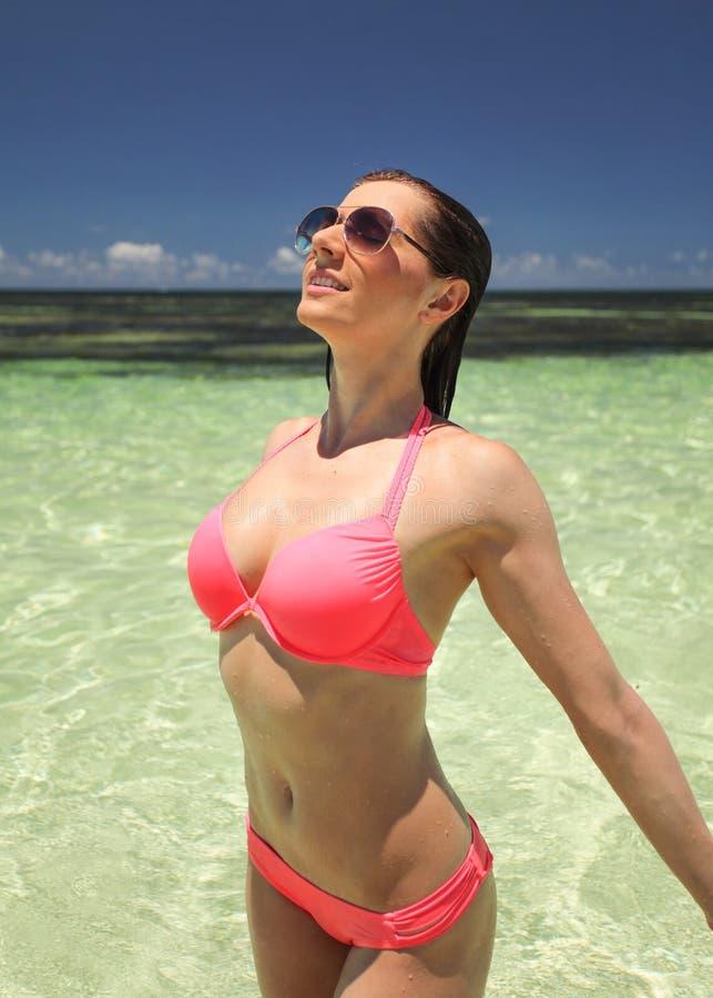 Mujer joven atractiva en biking rosado y gafas de sol foto de archivo