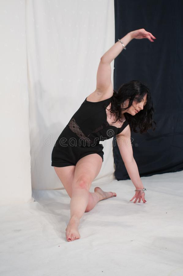Mujer joven atractiva en cuerpo negro en el fondo blanco Presentación de la danza imagen de archivo