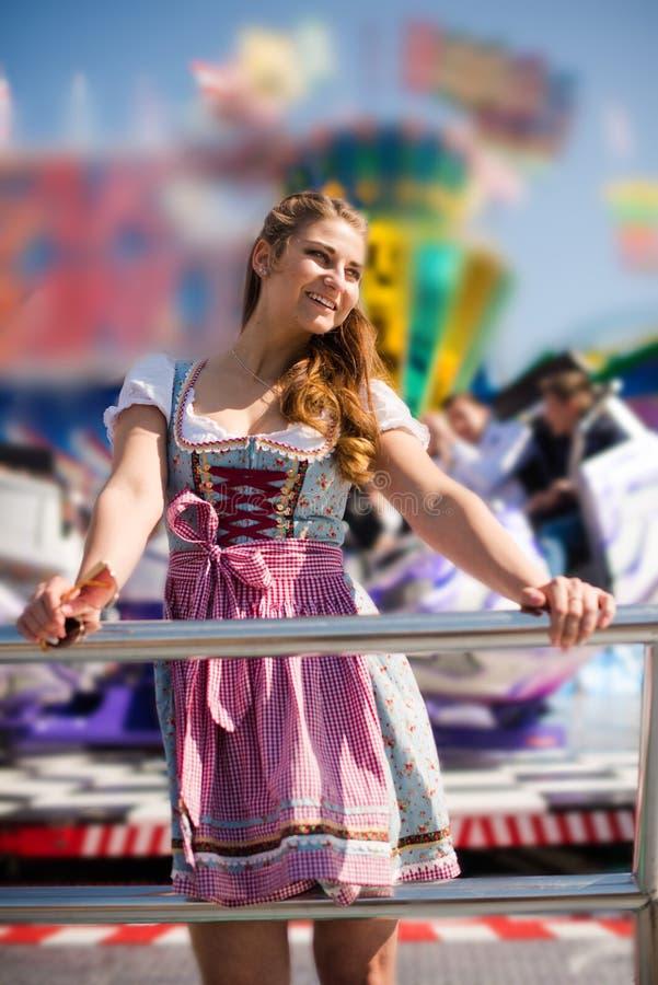 Mujer joven atractiva en el funfair alemán Oktoberfest con el vestido tradicional del dirndl imagen de archivo