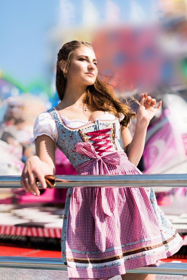 Mujer joven atractiva en el funfair alemán Oktoberfest con el vestido tradicional del dirndl fotos de archivo libres de regalías