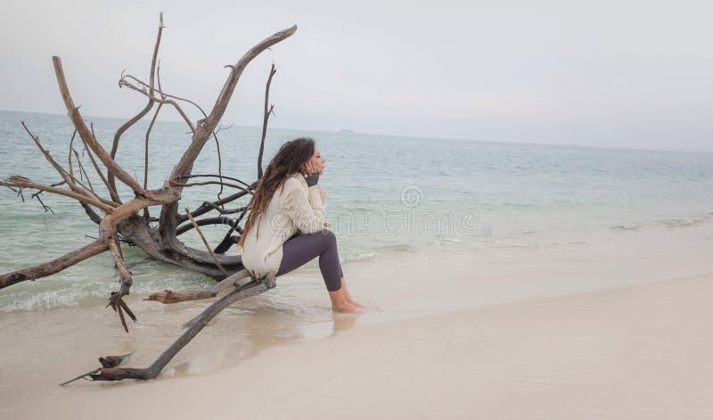 Mujer joven atractiva en el suéter que se sienta en la playa fotos de archivo libres de regalías
