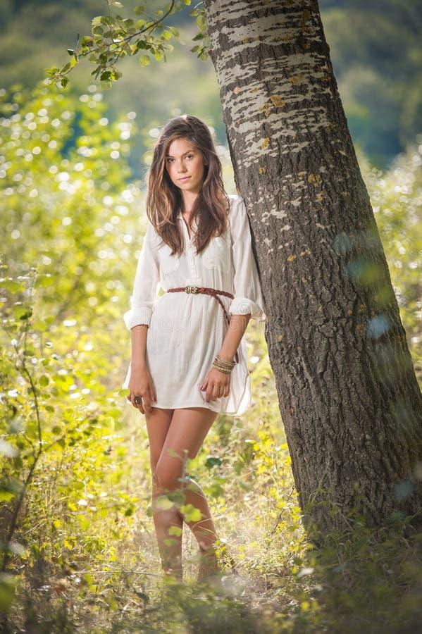 Mujer joven atractiva en el vestido del cortocircuito del blanco que presenta cerca de un árbol en un día de verano soleado Mucha imagen de archivo libre de regalías