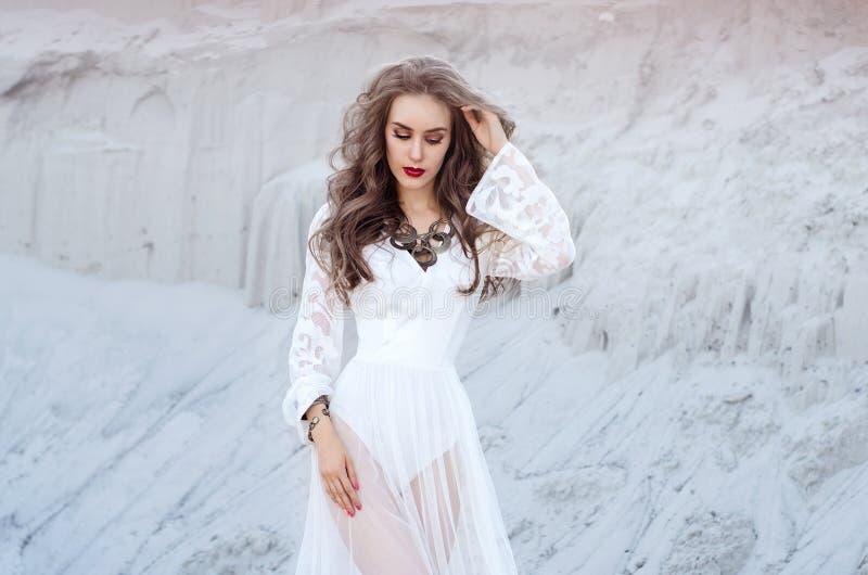 Mujer joven atractiva en el vestido largo blanco en el desierto Boho S foto de archivo