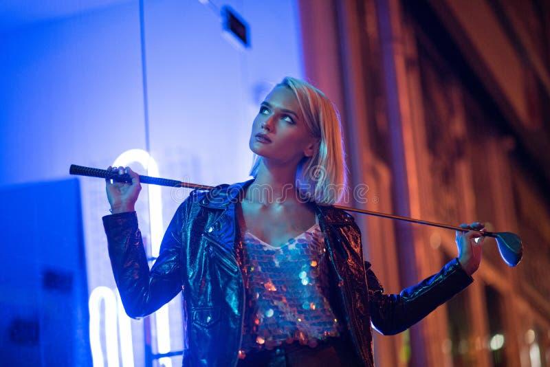 mujer joven atractiva en la situación de la chaqueta de cuero en la calle en la noche bajo luz y sostenerse azules imagen de archivo libre de regalías