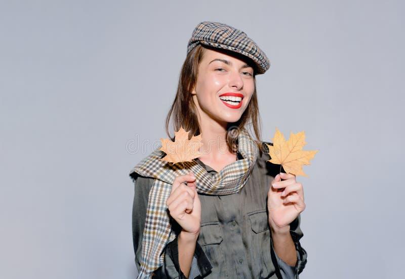 Mujer joven atractiva en ropa estacional con la hoja de oro El humor del otoño y el tiempo son calientes y soleados y lluvia imagen de archivo