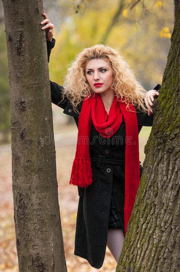 Mujer joven atractiva en un lanzamiento de la moda del otoño. Chica joven de moda hermosa con la bufanda roja en el parque. Mujere fotografía de archivo libre de regalías