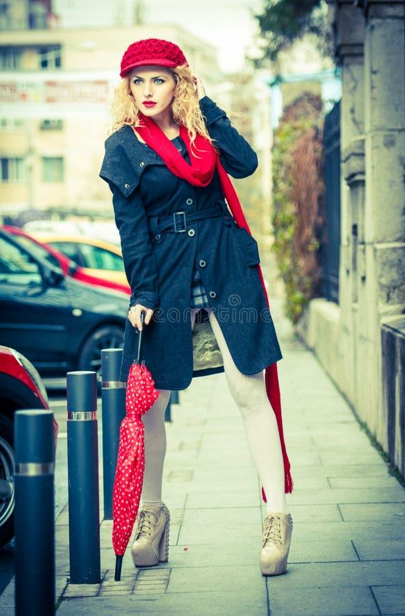 Mujer joven atractiva en un tiro de la moda del invierno. Chica joven hermosa con el paraguas rojo en la calle foto de archivo libre de regalías