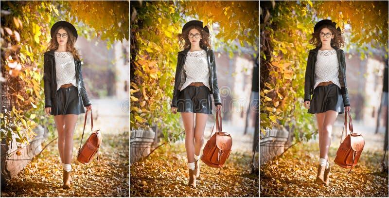 Mujer joven atractiva en un tiro otoñal al aire libre Colegiala de moda hermosa con la mochila de cuero que presenta en parque fotografía de archivo