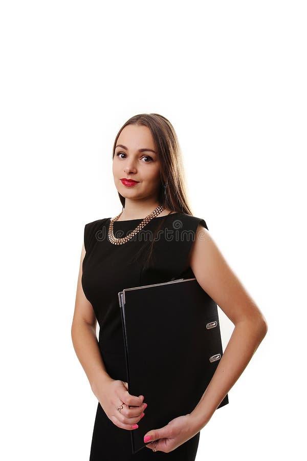 Mujer joven atractiva en un vestido negro que sonríe y que mira c imagen de archivo