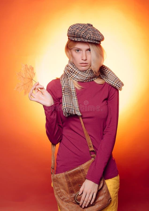 Mujer joven atractiva en una hoja de oro del whith estacional de la ropa La muchacha que lleva en oto?o viste el d?a soleado del  foto de archivo libre de regalías