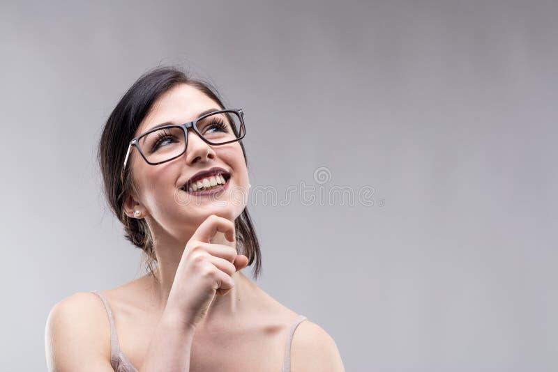 Mujer joven atractiva feliz que se coloca que sueña despierto fotos de archivo libres de regalías