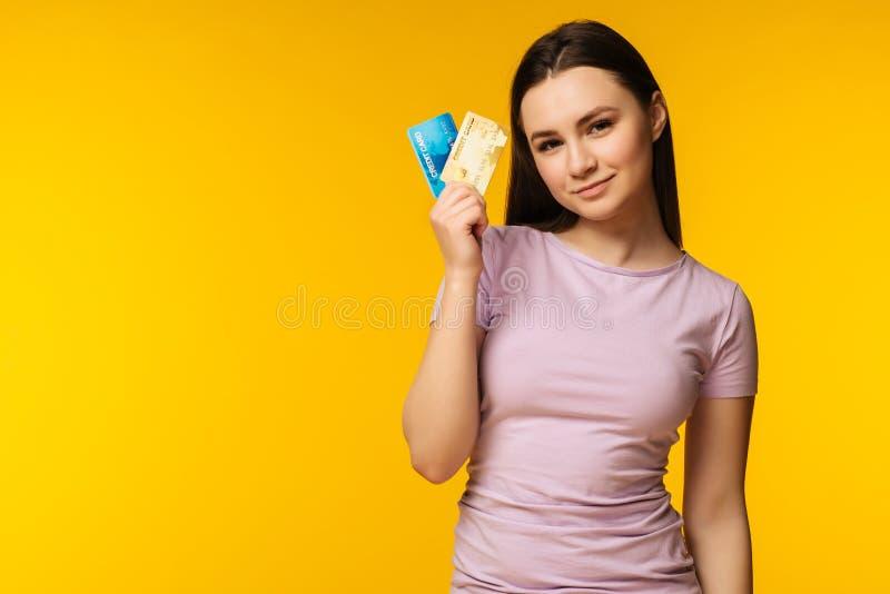 Mujer joven atractiva feliz que sostiene y que muestra la tarjeta de crédito dos sobre fondo amarillo fotografía de archivo