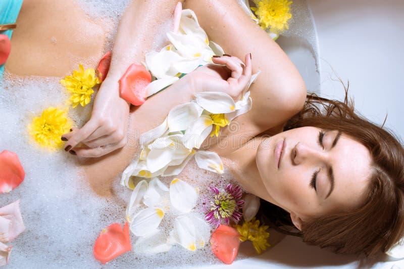 Mujer joven atractiva hermosa que tiene baño con los pétalos de la flor fotografía de archivo libre de regalías