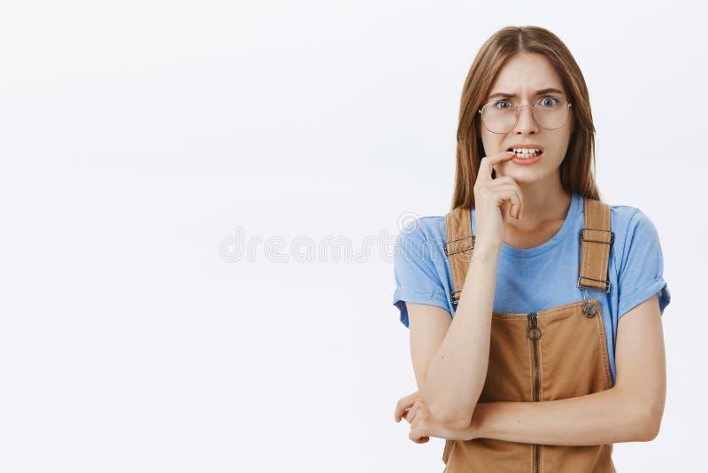 Mujer joven atractiva incierta preocupada con el pelo de la castaña en vidrios y guardapolvos que muerde el finger y la mirada qu imagenes de archivo