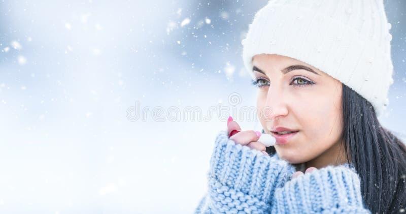 Mujer joven atractiva l labios de protección con protector labial en tiempo nevoso y congelado fotos de archivo