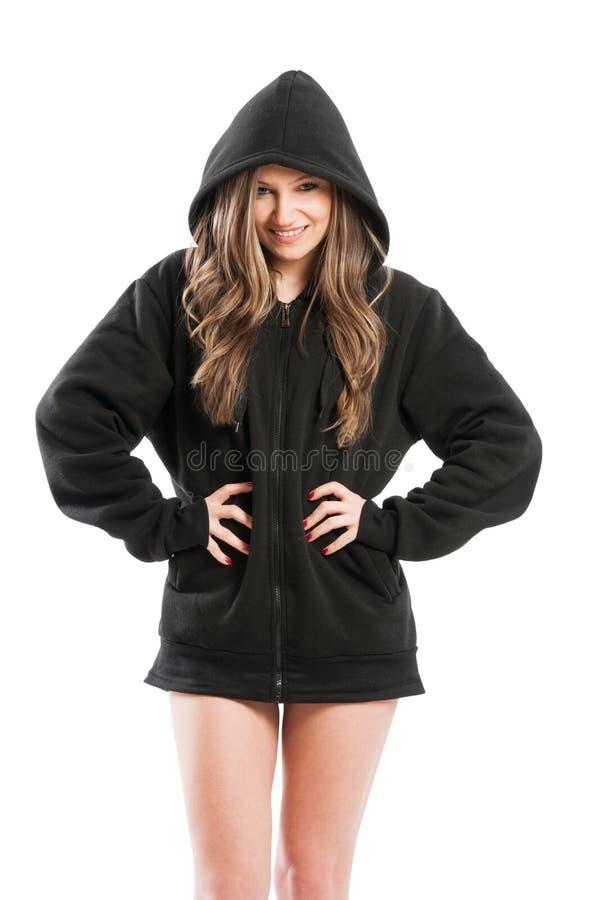 Mujer joven atractiva, linda, rizada y adorable que lleva una sudadera con capucha imagen de archivo