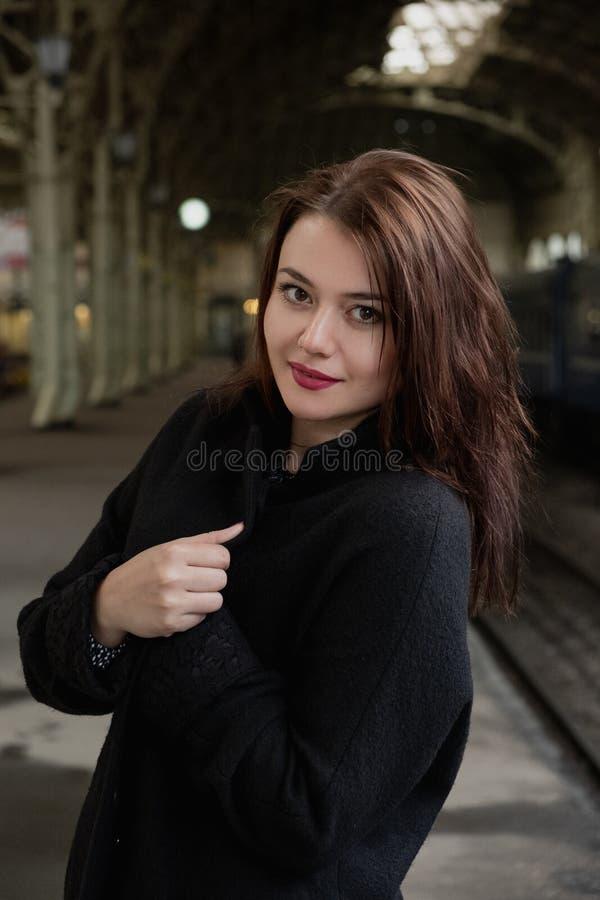 Mujer joven atractiva millenial en ropa negra y un sombrero y vidrios en el ferrocarril al lado del tren foto de archivo