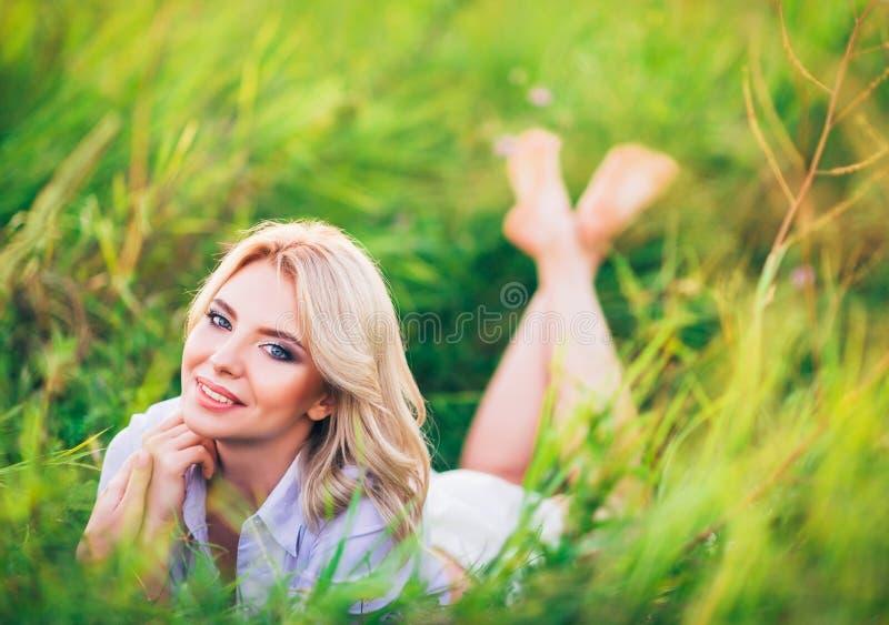 Mujer joven atractiva positiva que miente entre hierba verde fotografía de archivo