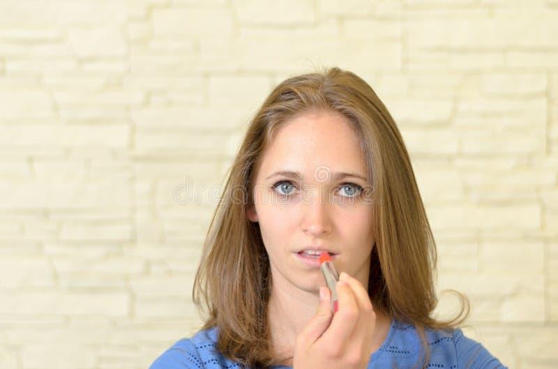 Mujer joven atractiva que aplica el lápiz labial fotografía de archivo
