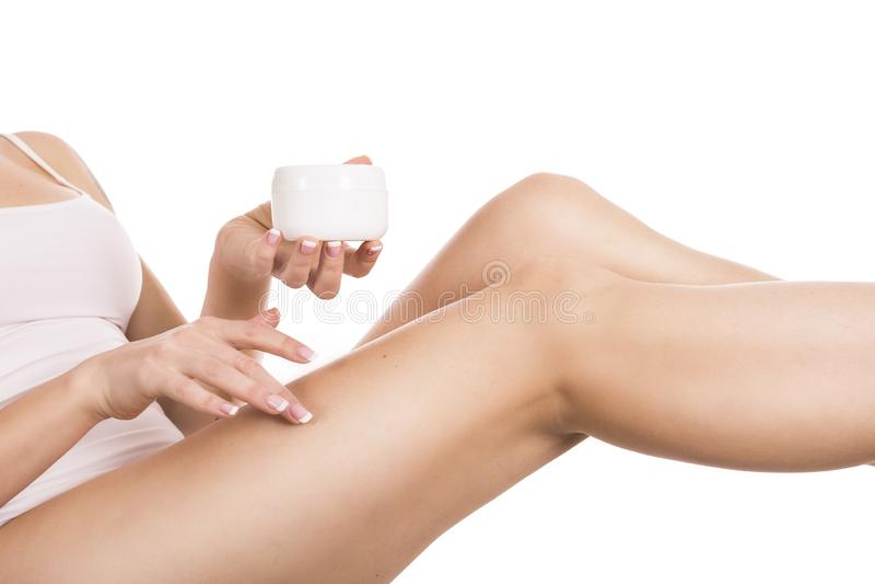 Mujer joven atractiva que aplica la crema a sus piernas aisladas en blanco foto de archivo