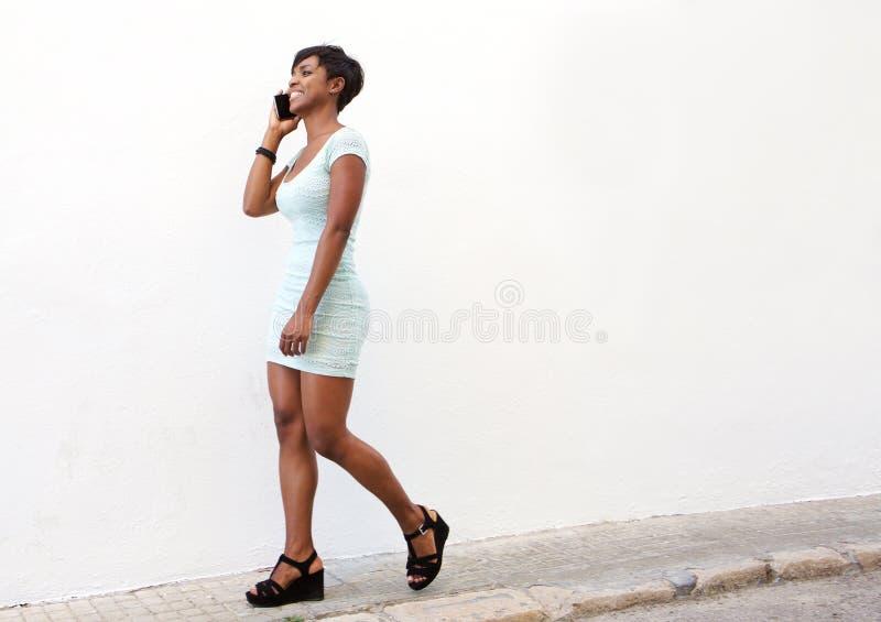 Mujer joven atractiva que camina en la calle con el teléfono celular imagen de archivo libre de regalías