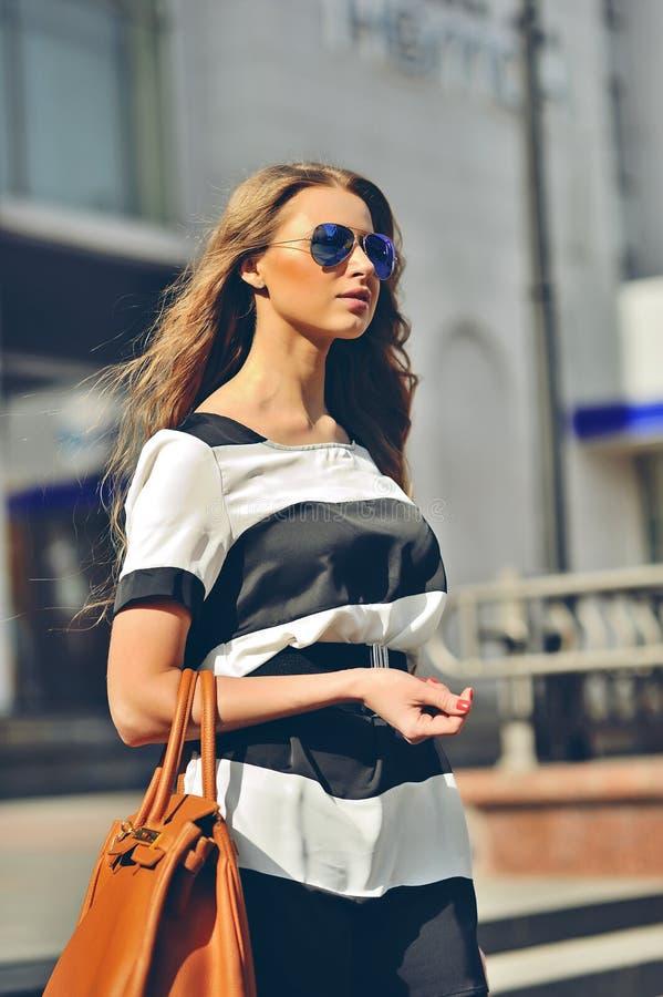 Mujer joven atractiva que camina en una calle foto de archivo libre de regalías