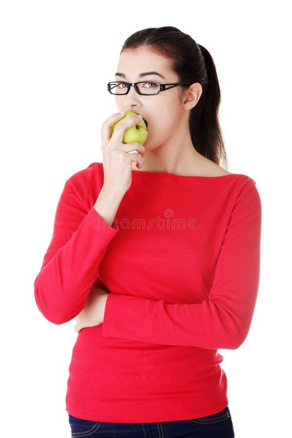 Mujer joven atractiva que come la manzana verde. fotografía de archivo libre de regalías