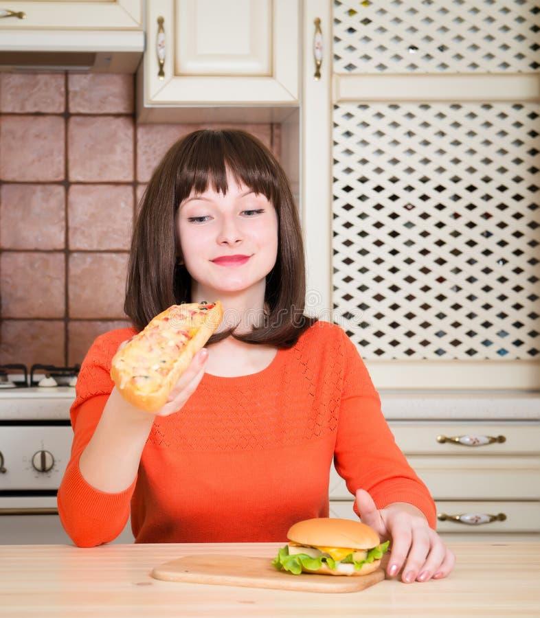 Mujer joven atractiva que come la pizza y la hamburguesa del pan francés foto de archivo