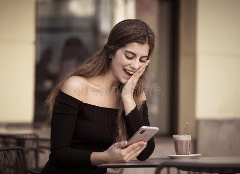 Mujer joven atractiva que comprueba el teléfono móvil feliz teniendo porciones de seguidores en su blog en línea fotos de archivo