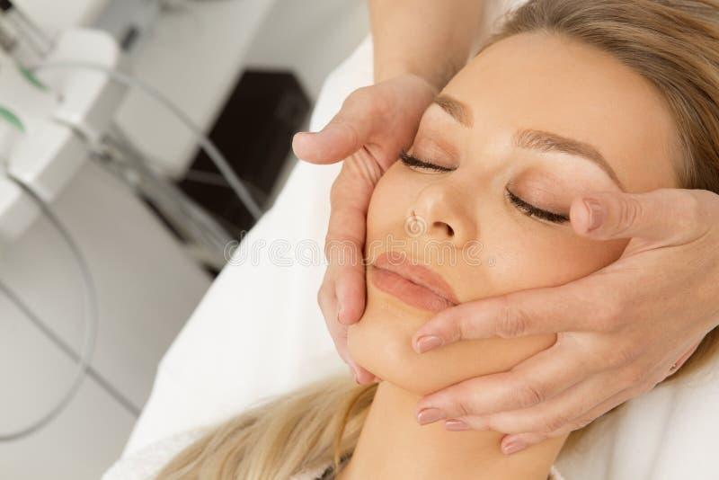 Mujer joven atractiva que consigue masaje de cara en el balneario foto de archivo
