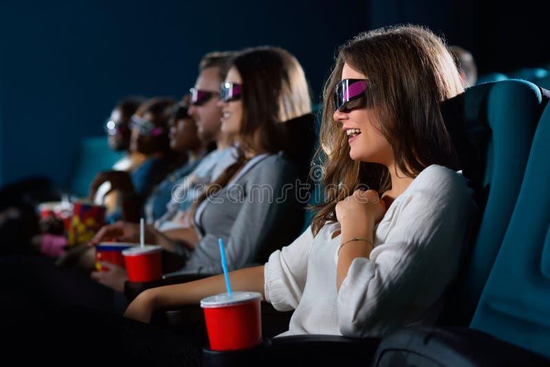 Mujer joven atractiva que disfruta de películas en el cine foto de archivo