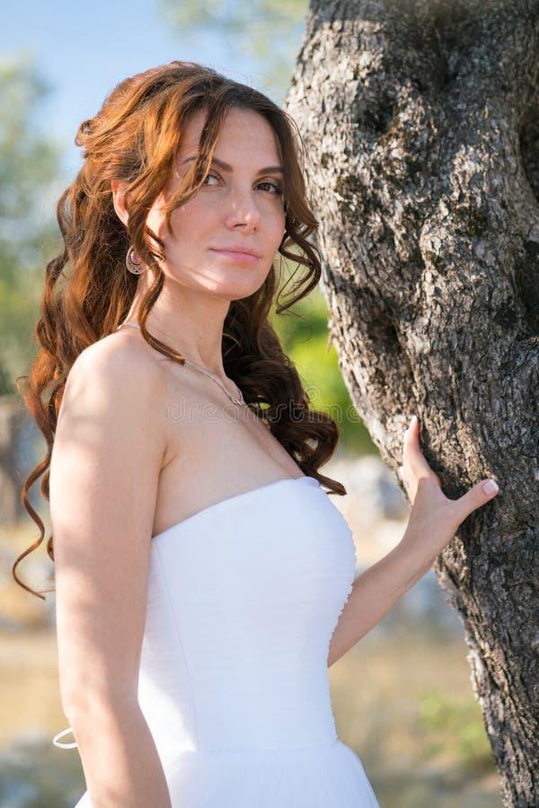 Mujer joven atractiva que disfruta de su tiempo afuera en olivos imagen de archivo libre de regalías
