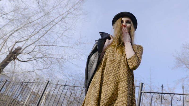 Mujer joven atractiva que disfruta de su tiempo afuera en parque con puesta del sol acci?n Mujer joven hermosa en sombrero que ca fotografía de archivo libre de regalías