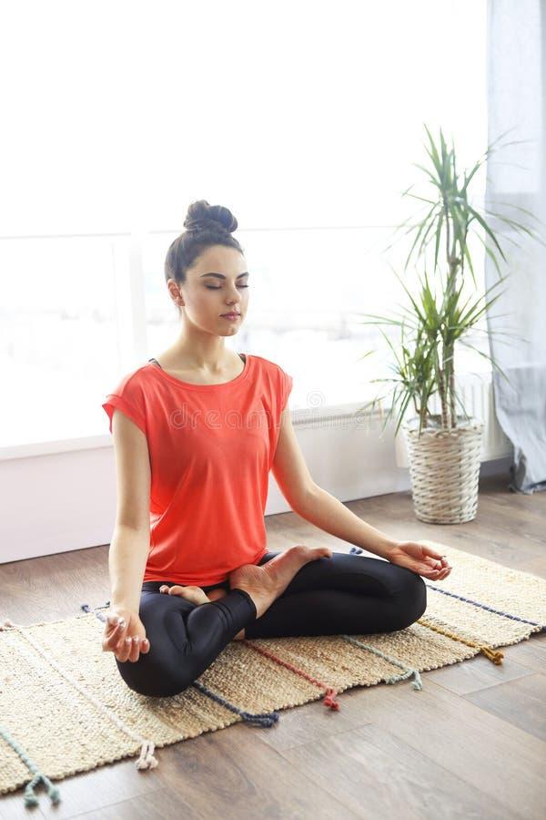 Mujer joven atractiva que ejercita y que se sienta en la posici?n de loto de la yoga mientras que descansa en casa imagen de archivo