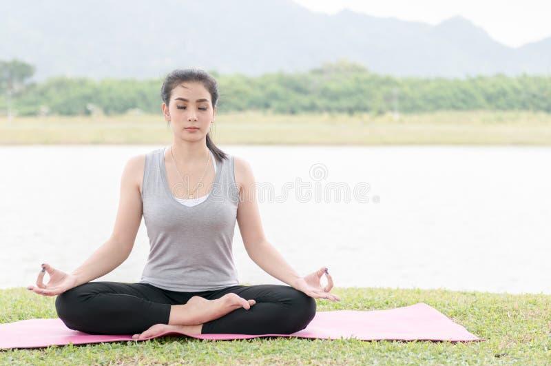 Mujer joven atractiva que ejercita y que se sienta en posi del loto de la yoga fotos de archivo libres de regalías
