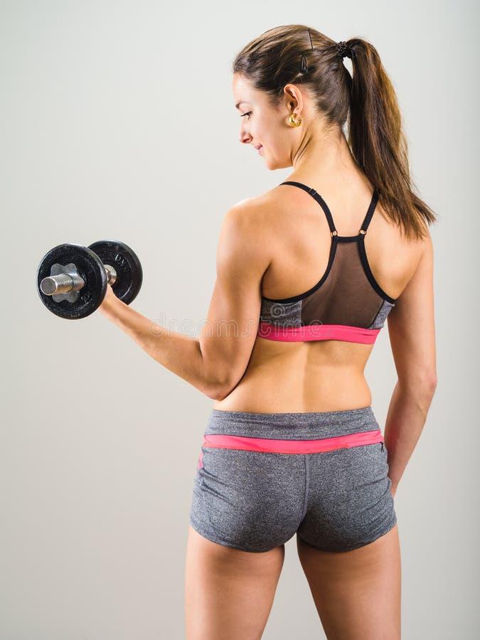 Mujer joven atractiva que hace el rizo de la pesa de gimnasia imagen de archivo libre de regalías
