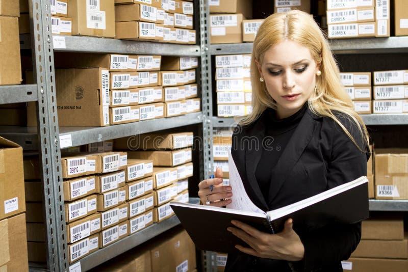 Mujer joven atractiva que hace inventario fotos de archivo