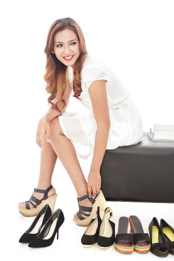 mujer joven atractiva que intenta en varios pares de nuevos zapatos fotos de archivo
