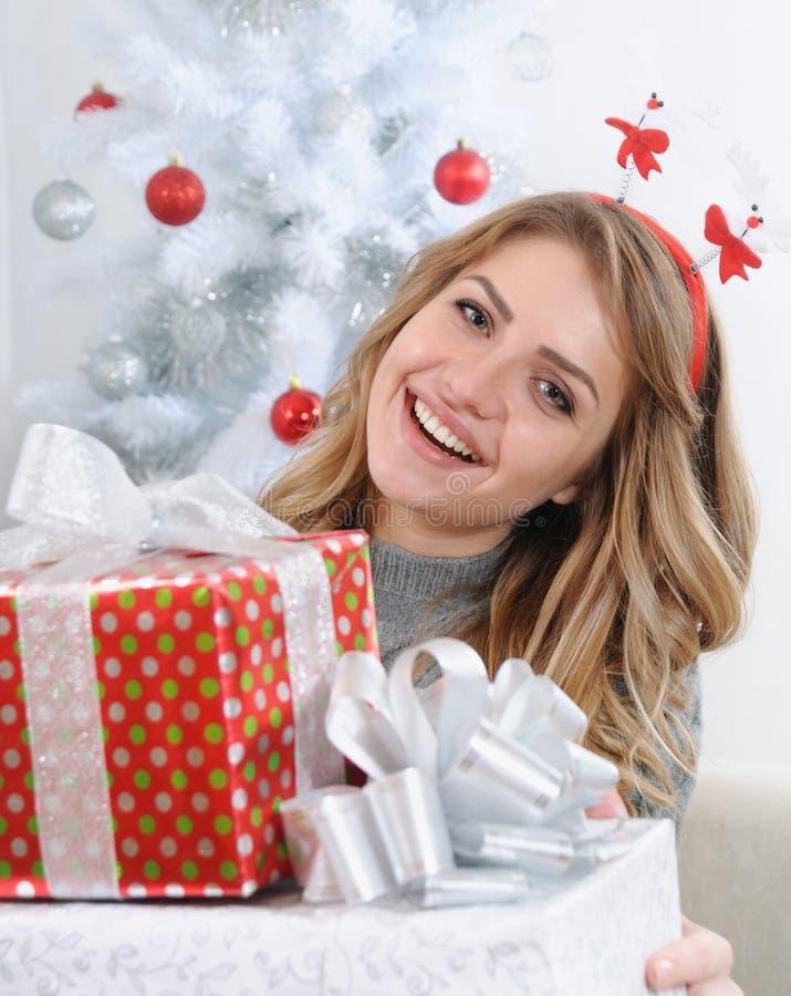 Mujer joven atractiva que le da los regalos para la Navidad fotos de archivo libres de regalías