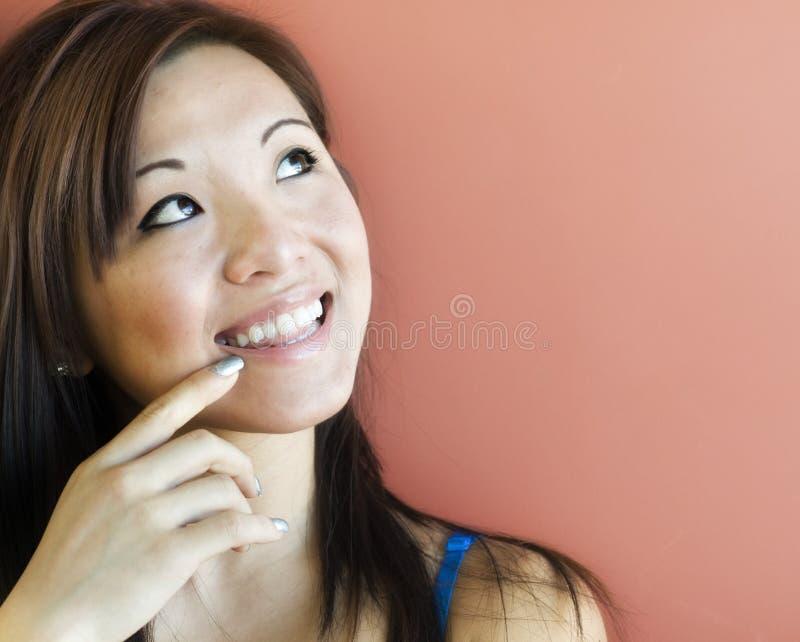 Mujer joven atractiva que mira hacia arriba imagen de archivo
