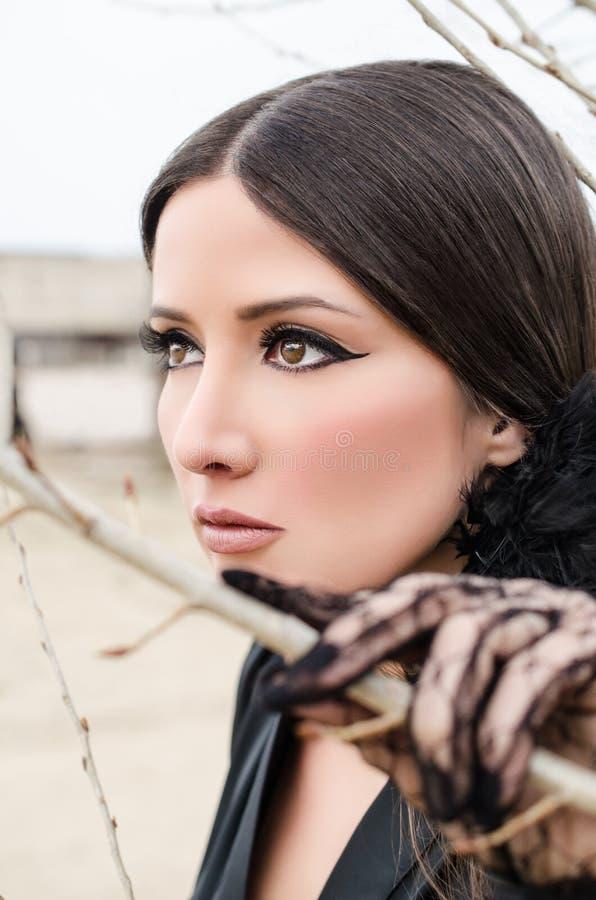 Mujer joven atractiva que mira a través de ramas de la primavera fotografía de archivo