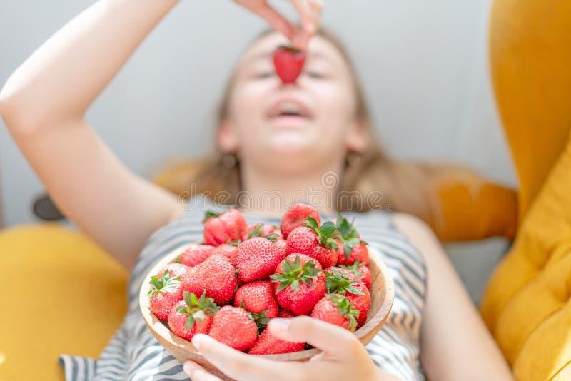 Mujer joven atractiva que pone en el sof? en una sala de estar casera de la sala de estar, comiendo la fresa fresca fotografía de archivo libre de regalías