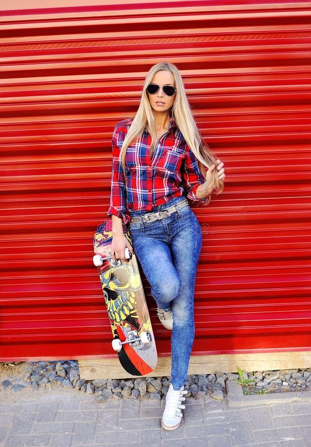 Mujer joven atractiva que presenta con el monopatín en una pared roja imagen de archivo
