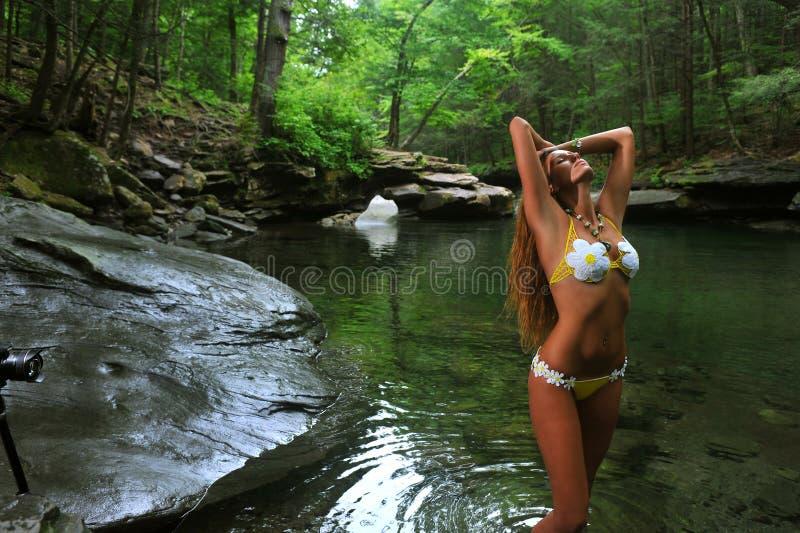 Mujer joven atractiva que presenta en bikini del diseñador en la ubicación exótica del río de la montaña foto de archivo