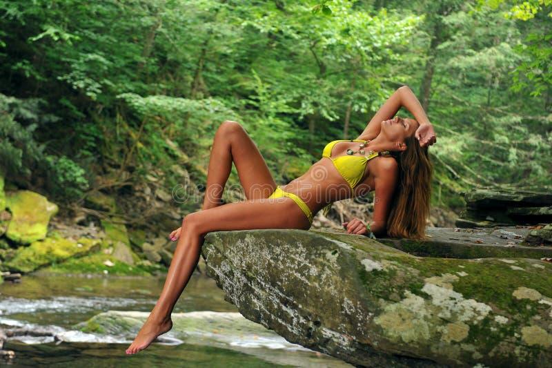 Mujer joven atractiva que presenta en bikini del diseñador en la ubicación exótica del río de la montaña fotografía de archivo libre de regalías