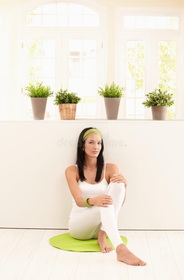 Mujer joven atractiva que presenta en suelo de la sala de estar imagenes de archivo