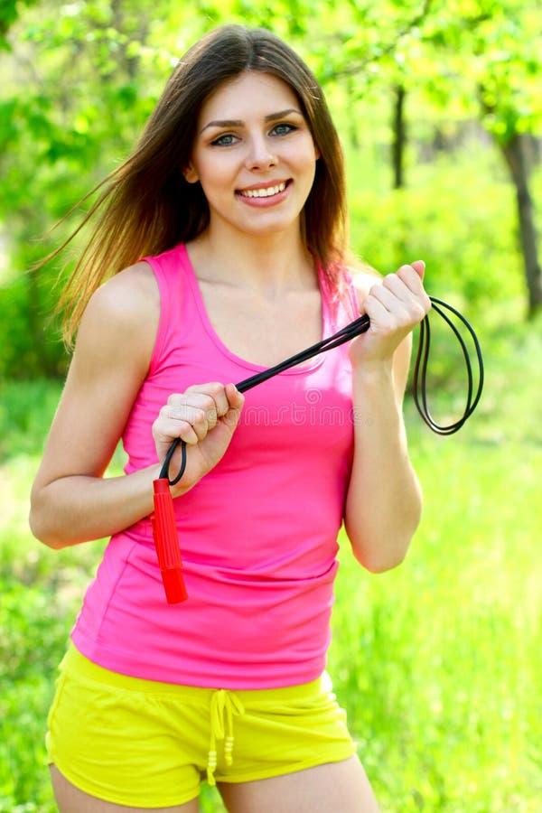 Mujer joven atractiva que presenta en un parque con una cuerda que salta foto de archivo